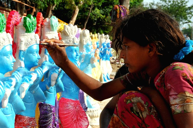 An artist busy painting idols of lord Krishna ahead of Krishna Janmashtami in Jaipur on Aug 13, 2014.
