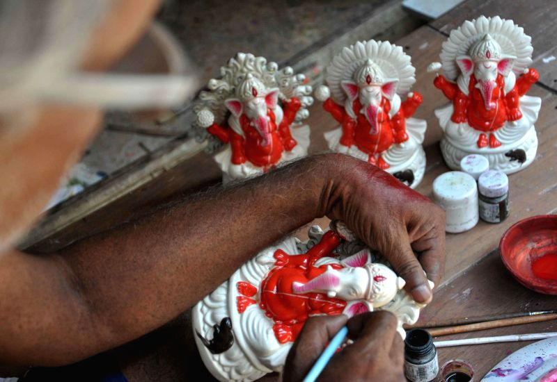 An artist gives final touches to idols of lord Ganesh ahead of Bengali New Year in Kolkata on April 14, 2014.