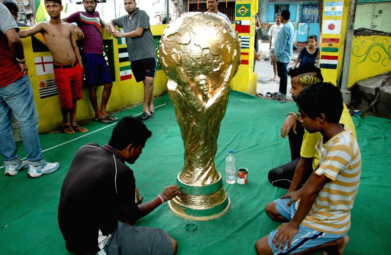 An artist gives finishing touch to a replica of FIFA World Cup in Kolkata on June 28, 2014.