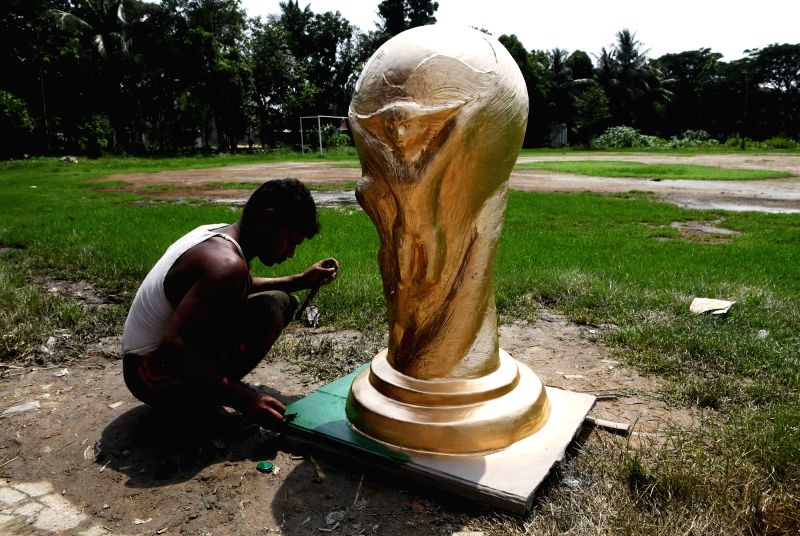 An artist gives finishing touches to a clay model of FIFA World Cup trophy in Kolkata, on June 13, 2018.
