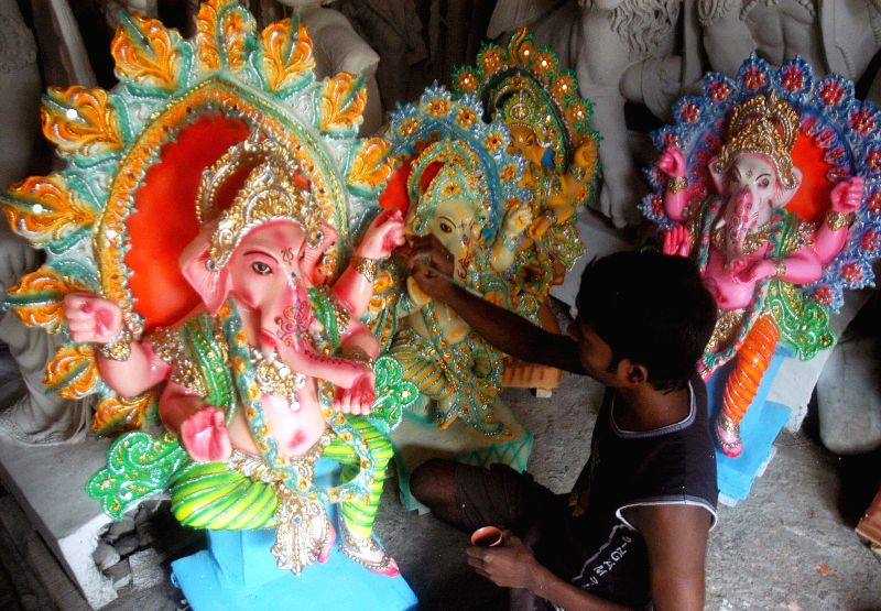 An artist gives finishing touches to a Ganesh idol at a Kumartuli workshop ahead of Ganesh Chaturthi in Kolkata on Aug 25, 2014.
