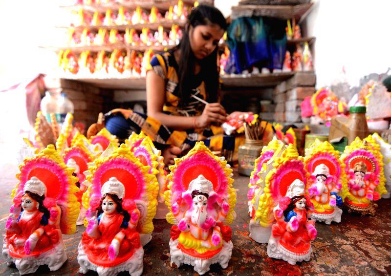 An artist making idol of Goddess Laxmi and Ganesh ahead of Diwali festival in Kolkata.