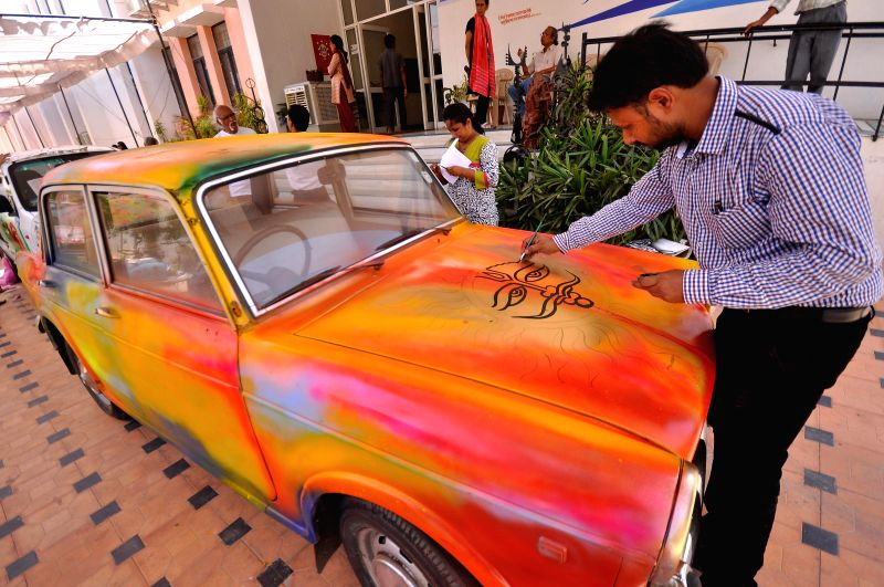 An artist paints a car during `Rang Malhar` - a programme organised by Rajasthan Lalit Kala Academy in Jaipur on July 10, 2014.