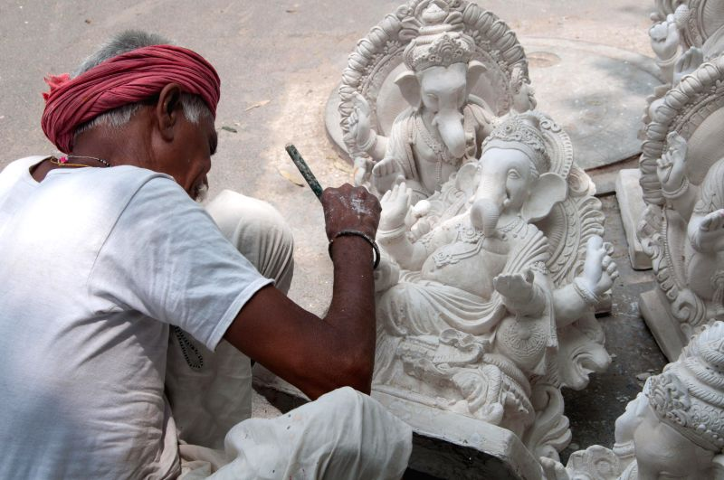 An artist paints an idol of Lord Ganesha  at a workshop ahead of Ganesh Chaturthi in New Delhi on Aug 26, 2014.