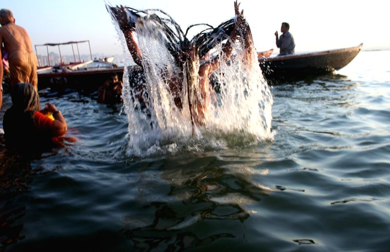 An ascetic takes a holy dip in the Ganga river on Budha Purnima in Varanasi on May 14, 2014.