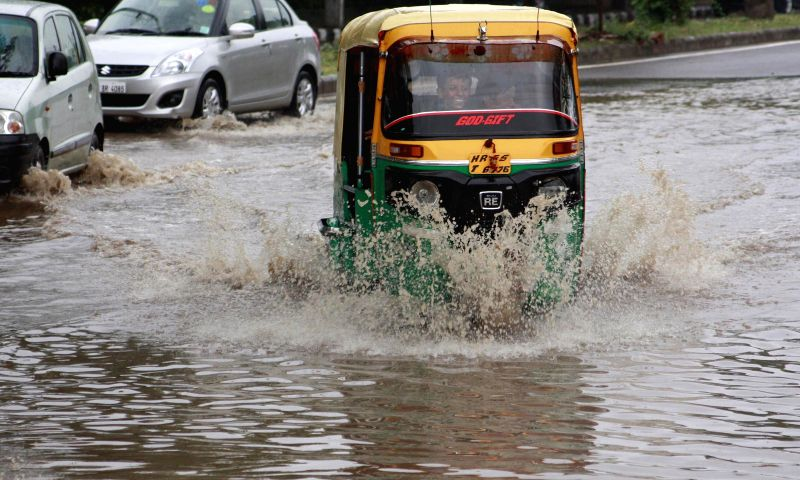 An auto-rickshaw struggles through a flooded road in Gurgaon on Sept 3, 2014.