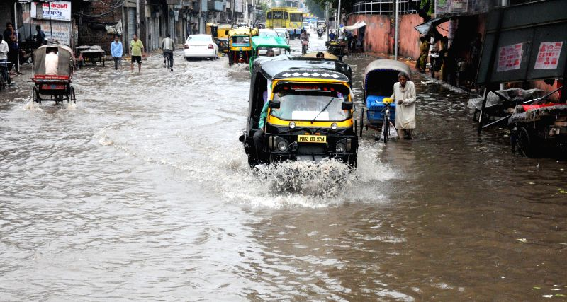 An auto rickshaw  struggles through flooded streets of Amritsar after heavy showers in Amritsar on Sept 4, 2014.