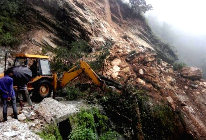 An earth-mover pressed into service to repair roads destroyed due to landslides in Pithoragarh district of Uttarakhand on July 29, 2016.