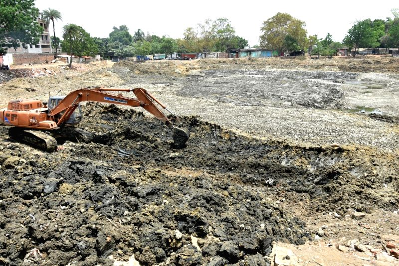 "An earth remover removes soil from a dried water pond on ""World Earth Day"" on the outskirts of Ranchi on April 22, 2017."