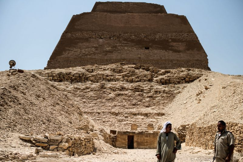 An Egyptian guide and a policeman stand outside of the Meidum Pyramid in Beni Suef Governorate, about 100 kilometers south to Cairo, Egypt, on Aug. 10, 2015. ...
