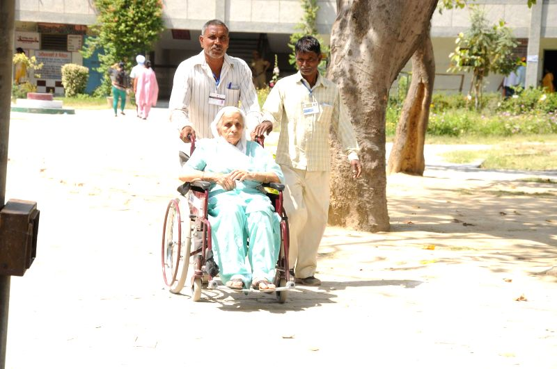 An elderly lady arrives at a polling booth on a wheel chair during the third phase of 2014 Lok Sabha Polls in New Delhi on April 10, 2014. Elections are being held in 91 parliamentary constituencies .
