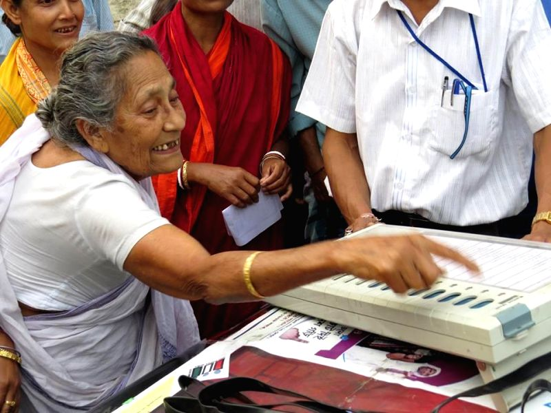 An elderly lady gets acquainted with an Electronic Voting Machine (EVM) ahead of 2014 Lok Sabha Polls in West Bengal on April 16, 2014.