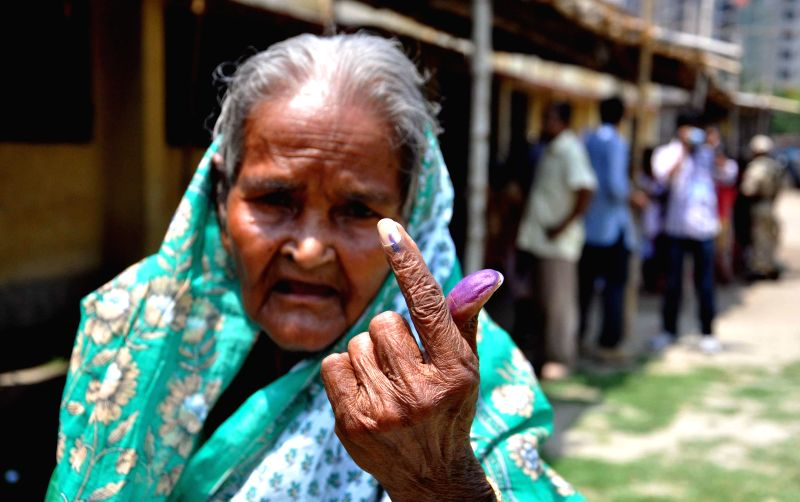 An elderly lady shows her fore finger marked with phosphorous ink after casting her vote at a polling booth during the ninth phase of 2014 Lok Sabha Polls in Kolkata on May 12, 2014.