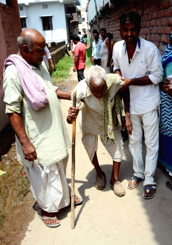 An elderly man being escorted to a polling booth during Patna Municipal Corporation elections on June 4, 2017.