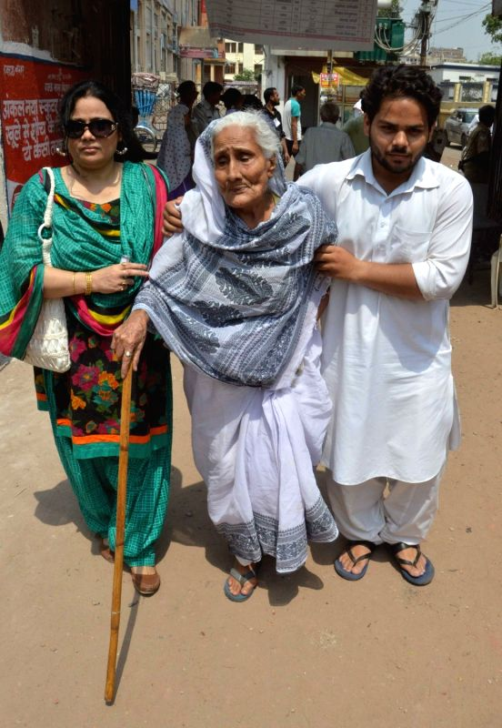 An elderly woman being escorted to a polling booth during Patna Municipal Corporation elections on June 4, 2017.