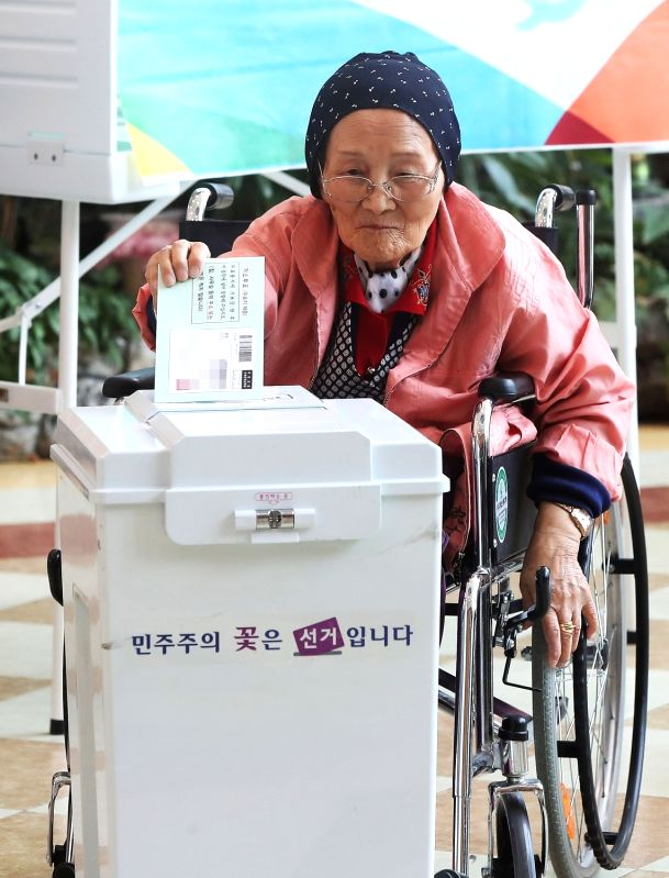 An elderly woman in a wheelchair casts a ballot at a sanatorium in the city of Suwon, just south of Seoul, on May 1, 2017, as she takes part in early voting for the May 9 presidential election ...