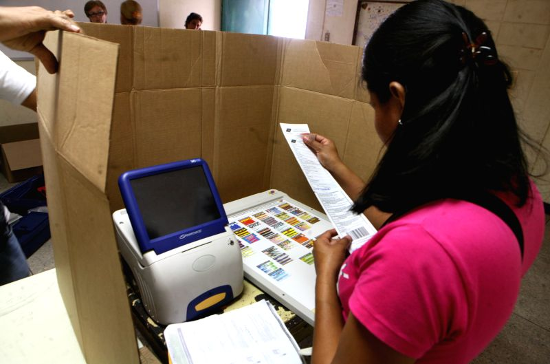 An electoral official checks a voting machine at a polling station in Maracaibo, Zulia State, Dec. 4, 2015. Venezuela will hold parliamentary elections on Sunday. ...