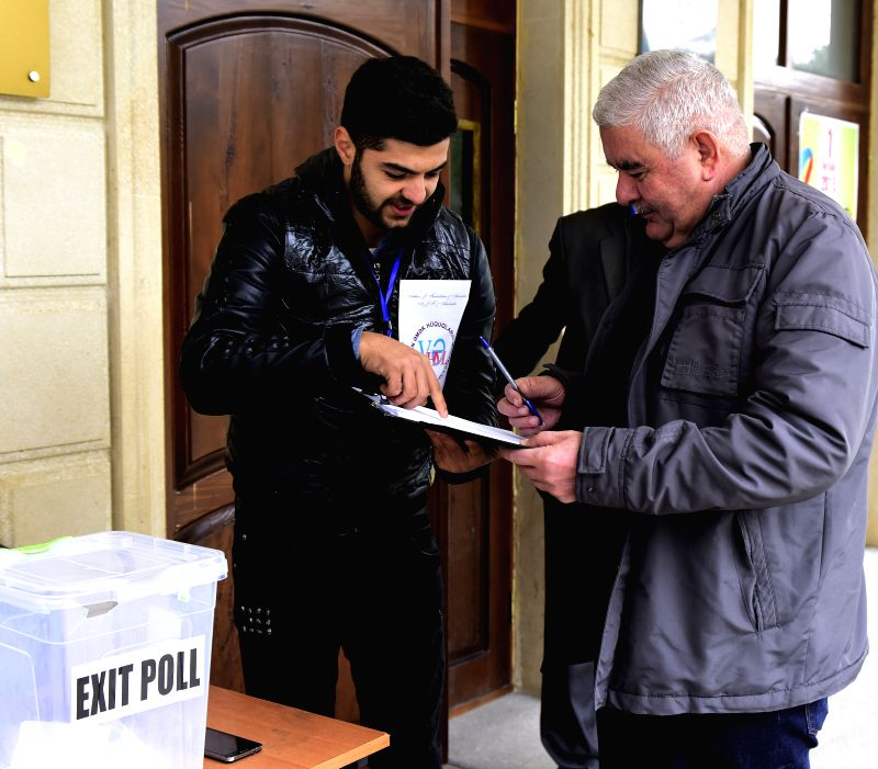 An electoral worker checks a voter's identity at a polling station in Baku, Azerbaijan held its 5th parliamentary elections early Sunday to pick the 125 deputies for ...
