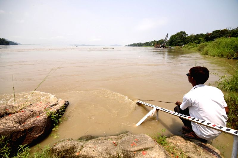 An employee of the Central Water Commission measures water level in Brahmaputra river, in Guwahati on June 3, 2017.
