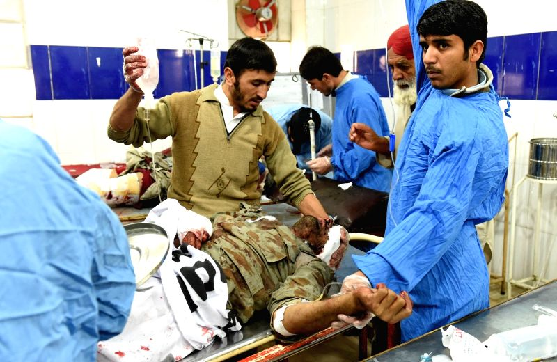 An injured security officer receives medical treatment at a hospital in southwest Pakistan's Quetta, Dec. 12, 2015. At least one security officer was killed and four ...