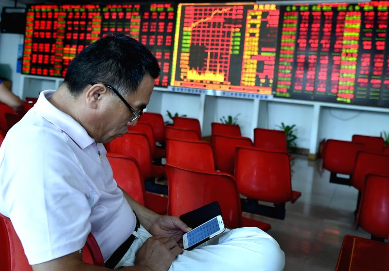 An investor looks through stock infomation at a securities firm in Haikou, capital of south China's Hainan Province, Aug. 10, 2015. The benchmark Shanghai Composite ...