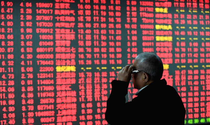 :An investor looks through stock information at a stock trading hall in Hangzhou, east China's Zhejiang Province, Nov. 4, 2015. China's stocks closed ...