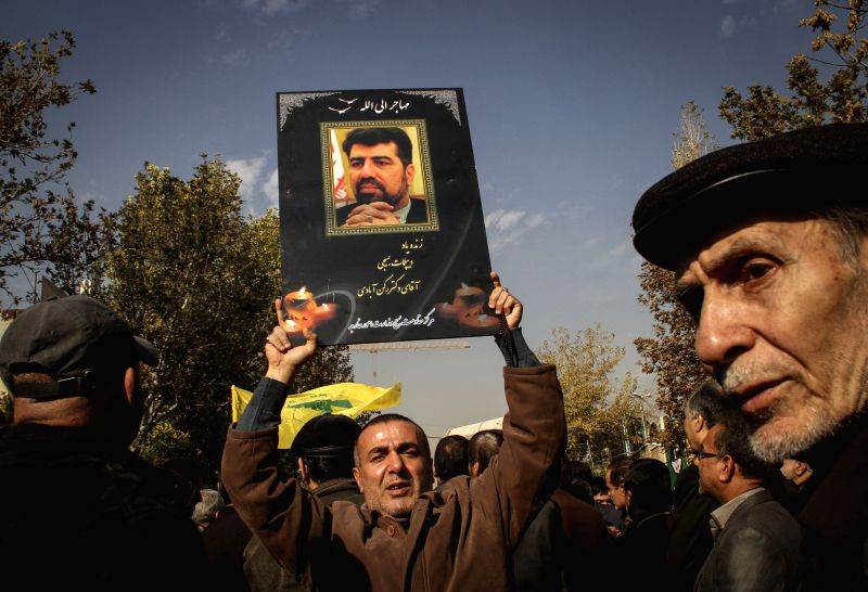An Iranian mourner holds up a poster of Iran's former ambassador to Lebanon Ghazanfar Roknabadi, who died in the Hajj stampede in Saudi Arabia in September, during ...