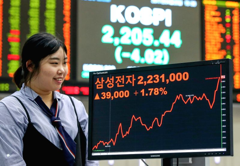 An official at the Korea Exchange in Seoul watches a monitor showing Samsung Electronics Co.'s price, which increased 1.78 percent to close at a record high of 2,231,000 won (US$1,962.18) on ...