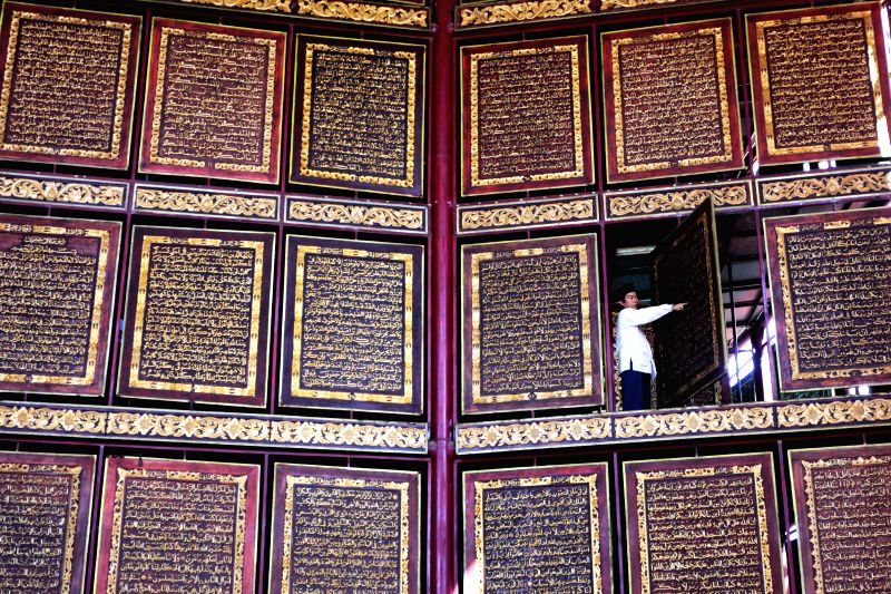 An official checks the largest wood carving of Koran during the Nuzul Al-Quran in Palembang, Indonesia, July 4, 2015. Nuzul Al-Quran is celebrated on the 17th day ...