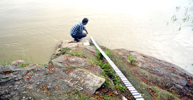 An official checks the water level of Brahmaputra river, which rose by 2 cms in 12 hours, in Guwahati on Aug 24, 2014.
