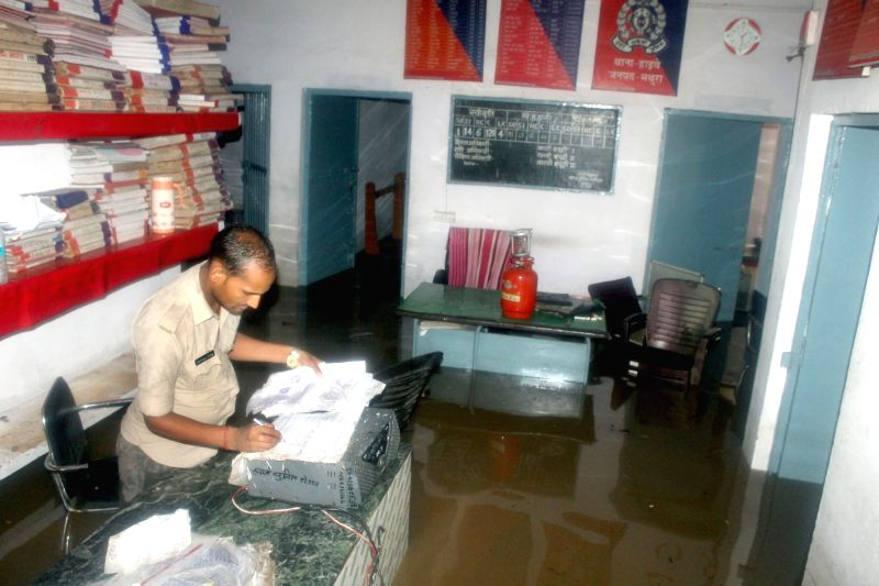 An policeman stands inside a police station which was flooded following heavy monsoon rains in Mathura on July 17, 2016.