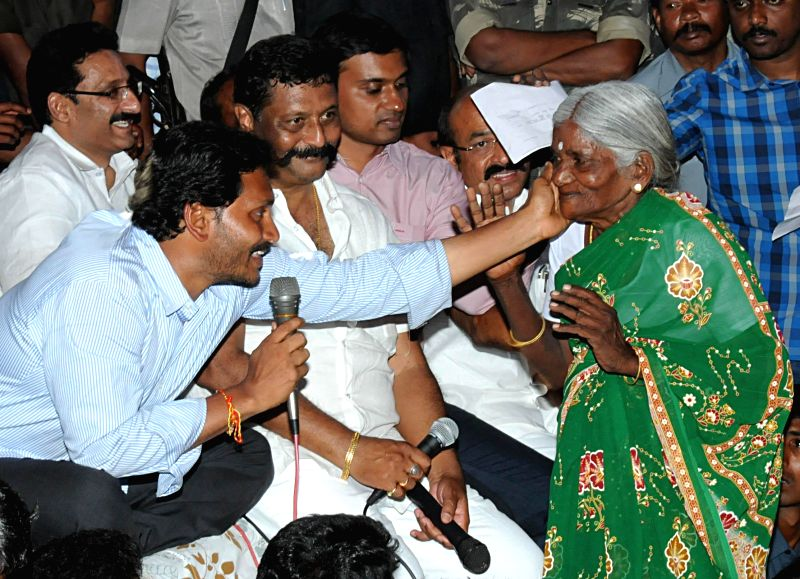 Anantapur : YSR Congress chief Y. S. Jaganmohan Reddy interacts with an elderly woman during a public meeting in Ramaraju Palli village of Andhra Pradesh's Anantapur district on Feb 27, 2015.