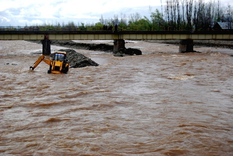 An earth mover stuck in the swollen Jhelum river in Anantnag on April 3, 2015.