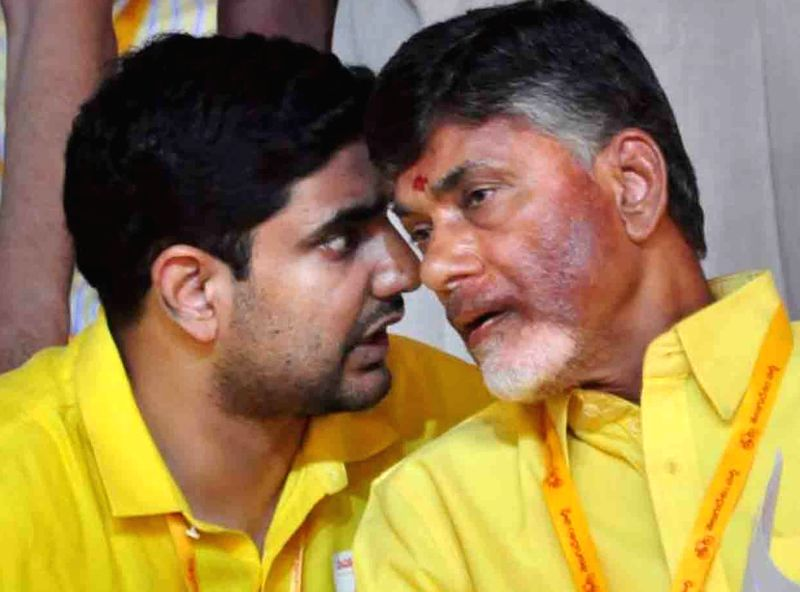 Andhra Pradesh Chief Minister and TDP chief N Chandrababu Naidu interacts with son Nara Lokesh during Telugu Desam Party's 'Mahanadu' -mega-convention- in Tirupathi on May 28, 2016. - N Chandrababu Naidu