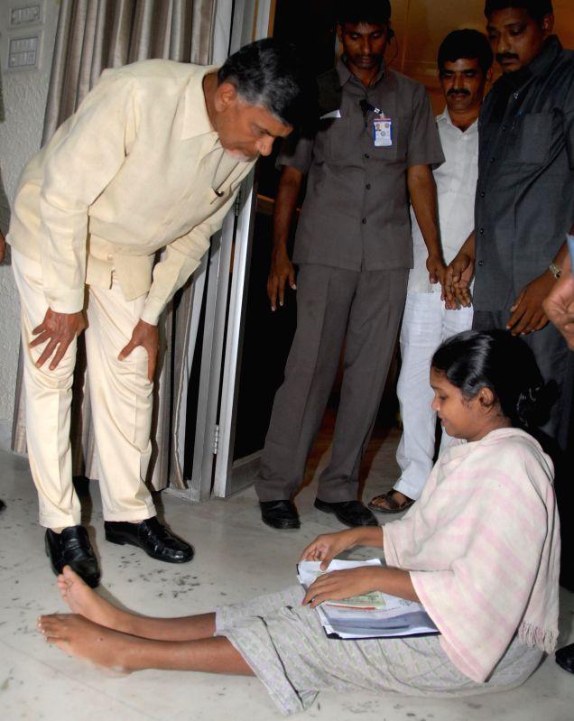 Andhra Pradesh Chief Minister N. Chandrababu Naidu interacts with a physically challenged girl from Kakinada in Andhra Pradesh, in Hyderabad on July 14, 2014. - N. Chandrababu Naidu