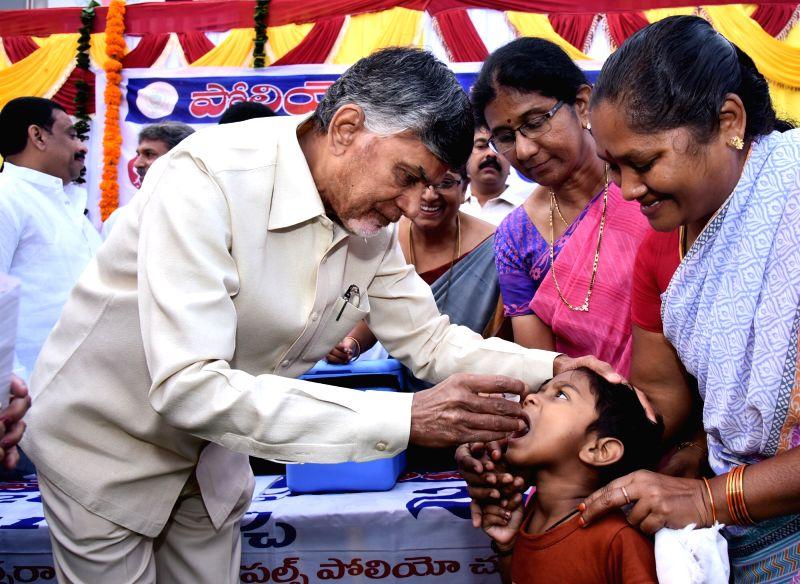 Andhra Pradesh chief Minister N. Chandrababu Naidu gives polio drops to a child during Pulse Polio programme in Vijayawada on Jan 28, 2018. - N. Chandrababu Naidu