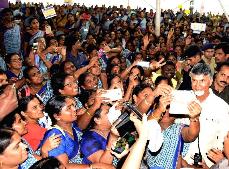 Andhra Pradesh Chief Minister N. Chandrababu Naidu poses for selfies with Anganwadi workers during an interactive session with them, in Vijayawada on July 12, 2018. - N. Chandrababu Naidu