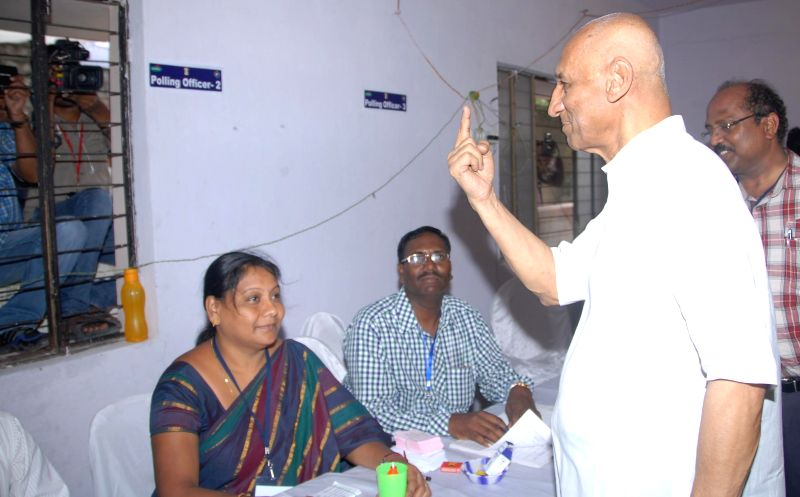Andhra Pradesh Governor ESL Narasimhan shows his fore finger marked with phosphorous ink after casting his vote at Anganwadi Center (ICDS) Rajnagar polling booth during the seventh phase of 2014 Lok .
