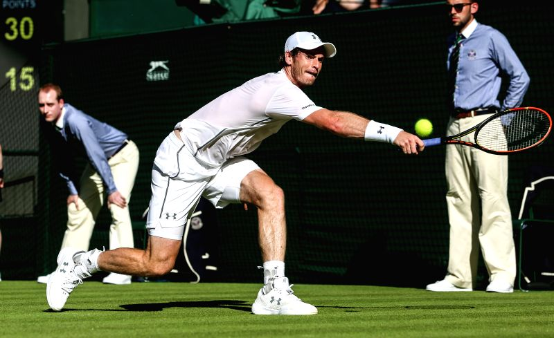 Andy Murray of Britain returns the ball to Mikhail Kukushkin of Kazakhstan during the men's singles first round match at 2015 Wimbledon Tennis Championships in ...