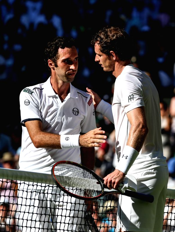 Andy Murray (R) of Britain shakes hands with  Mikhail Kukushkin of Kazakhstan after winning the men's singles first round match at 2015 Wimbledon Tennis ...