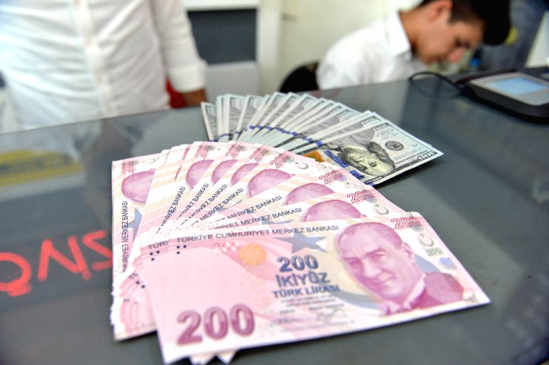ANKARA, Aug. 10, 2018 - A money changer shows U.S. Dollar and Turkish Lira banknotes at a currency exchange office in Ankara, Turkey, on Aug. 10, 2018. The Turkish lira on early Friday hit an ...