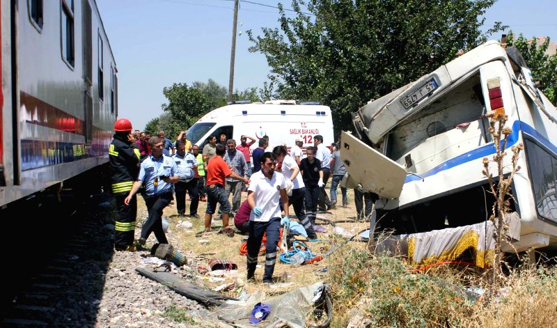 ANKARA, July 22, 2016 - Firefighters and medical workers work at the scene where a passenger train crashed with a minibus in Alasehir county of Manisa, southwestern Turkey, on July 22, 2016. Six ...