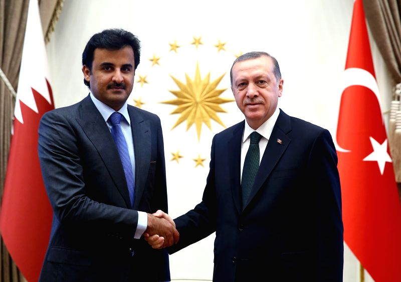 Sheikh Tamim bin Hamad al-Thani (L), the emir of Qatar, shakes hands with Turkish President Recep Tayyip Erdogan during his surprise visit in Ankara, Turkey, March ...