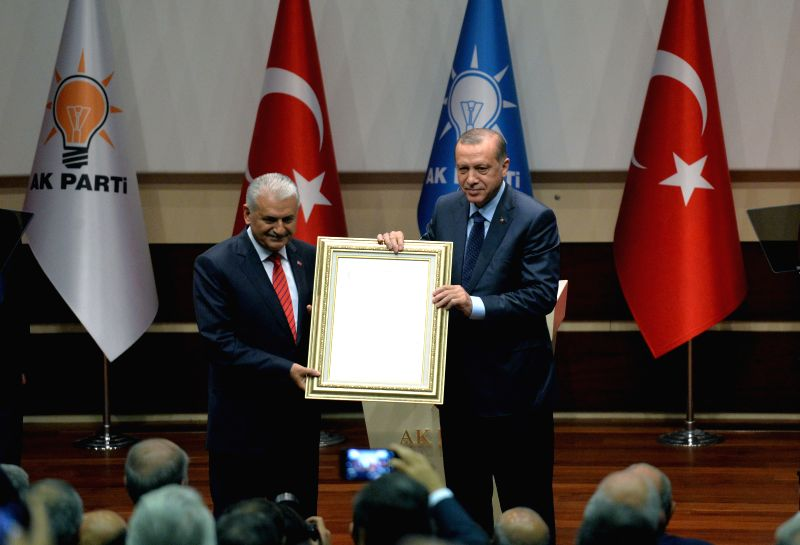 ANKARA, May 2, 2017 - Turkish Prime Minister Binali Yildirim (L) hands Turkish President Recep Tayyip Erdogan a party membership certificate confirming Erdogan's re-admittance to the ruling Justice ... - Binali Yildirim