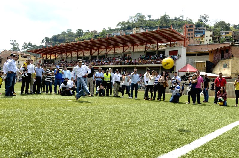 Image provided by the Colombia's Presidency shows the Colombian President Juan Manuel Santos (front) kicking the ball during the opening ceremony of the Juan ...