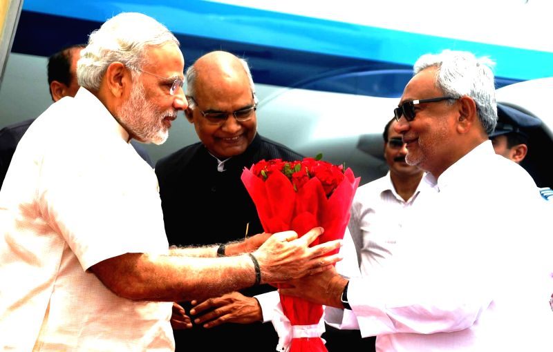 Ara (Bihar): Bihar Governor Ram Nath Kovind and Chief Minister Nitish Kumar welcome Prime Minister Narendra Modi on his arrival at Ara, in Bihar on Aug 18, 2015. - Nitish Kumar, Narendra Modi and Nath Kovind