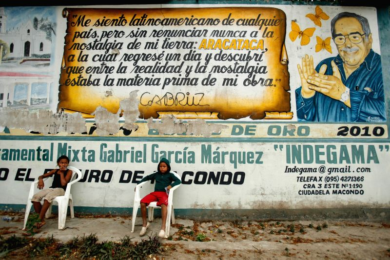 Two children rest in front of an allusive mural to the late Colombian writer Gabriel Garcia Marquez, in the town of Aracataca, Magdalena's department, Colombia, .
