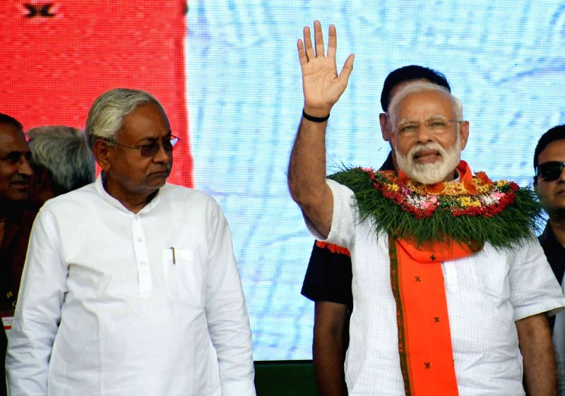 Araria: Prime Minister Narendra Modi waves at supporters during a public rally in Bihar's Araria, on April 20, 2019. Also seen Bihar Chief Minister Nitish Kumar.
