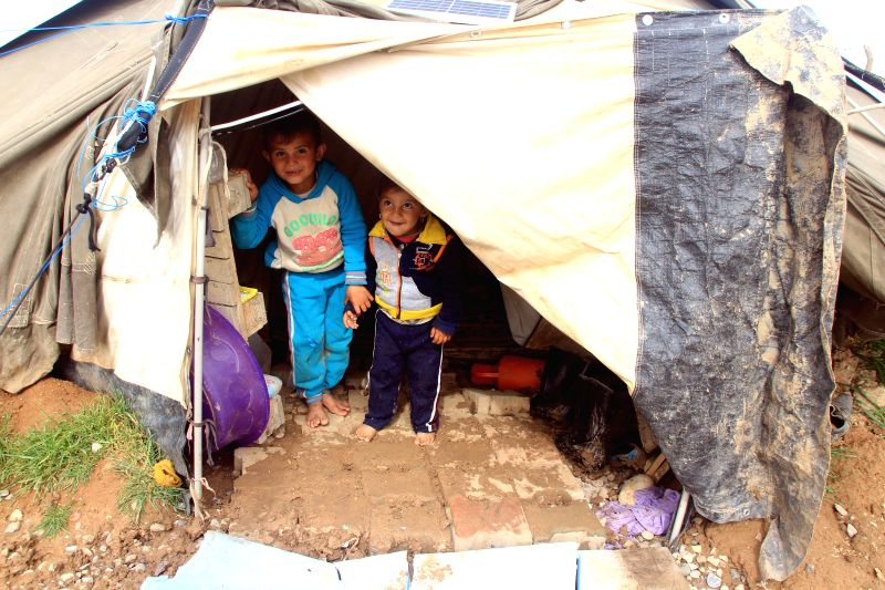 Children stand in their tent in a refugee camp at the outskirts of Arbil, capital of Kurdistan, northern Iraq, Feb. 21, 2015.