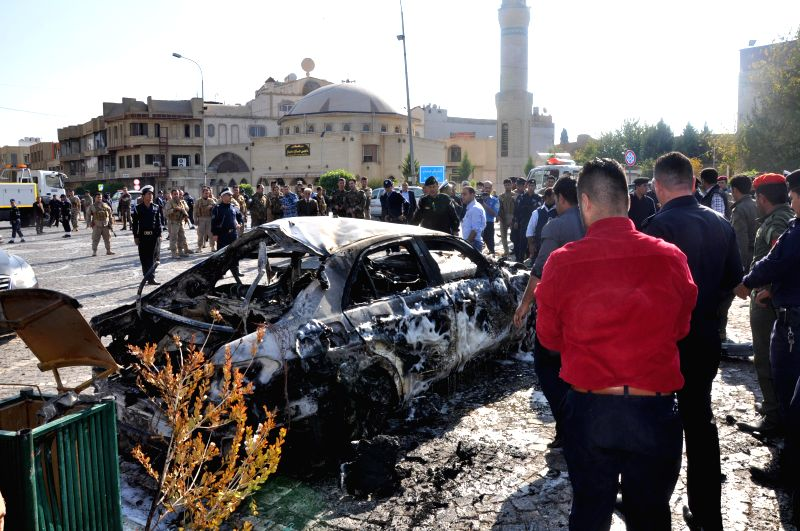 People gather at the site of a suicide bombing in the city of Arbil, capital of the semi-autonomous region of Kurdistan in northern Iraq, Nov. 19, 2014. A suicide car bomb attack struck the ...